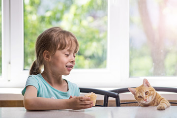 Little girl is sitting at the table with a red kitten, free space.