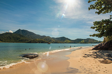 View of beach, sea and forest on sunny day in Ilha do Pelado, a tropical beach near Paraty, an amazing and historic town totally preserved in Rio de Janeiro State, southwestern Brazil. Retouched photo