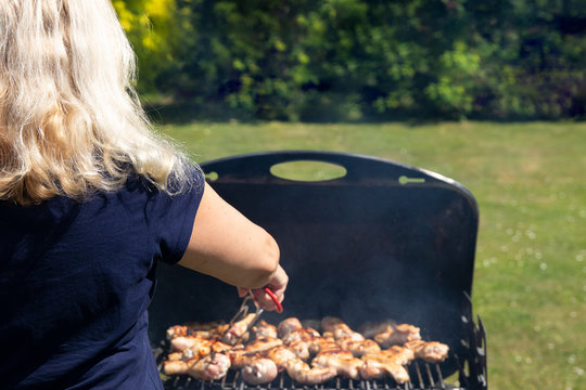 Woman is grilling chicken meat and using barbecue tongs. Concept food. BBQ.
