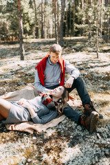 Pre-wedding photo shoot in the forest in nature, in the form of walking and traveling. Beauty of the North and Russia. Loving people and beautiful scenery. They laugh, sit and smile. Beautiful couple