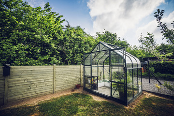 Greenhouse in a garden with trees behind