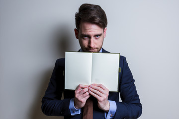 Angry business man showing blank note. Studio portrait isolated.