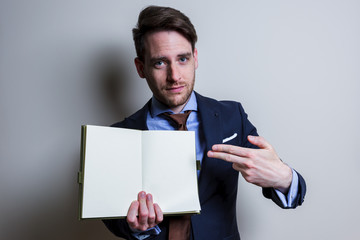 Business man showing blank note. Studio portrait isolated.