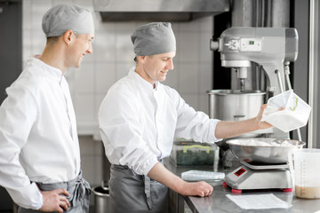 Two handsome male confectioners in uniform weighing ingredients for baking at the manufacturing