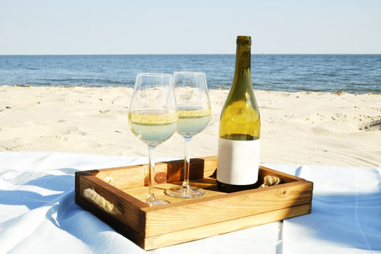 Romantic dinner composition with expensive bottle of white wine, blank label and two glasses on wooden tray at the white sandy beach, ocean. Sea view. Close up, background, copy space.
