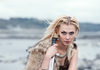 A woman is a warrior in a wolf's skin with a sword in her hands. Girl of the Vikings. Reconstruction of the medieval scene.