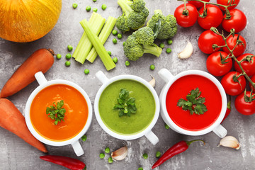 Vegetable cream soup with parsley on grey wooden table
