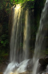 A stunning waterfall illuminated by the sun in jungles of Cambodia. The scenery in the waterfall area in the tropical rainforest of Phnom Kulen national Park one of the attractions in Siem Reap region