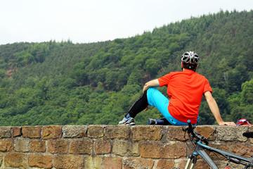 Mountainbiker macht Pause auf einer Burgmauer