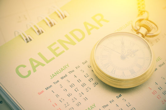 Calendar planner stationery concept : Pocket watch on a paper desk calendar. A calendar is a system of organizing days for commercial or administrative purposes by giving names to a period of time.