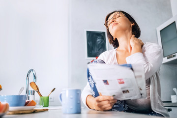Woman has a neck pain when reads a magazine on the kitchen at morning time