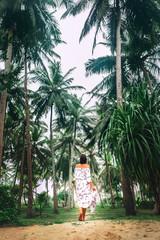 Woman in long white dress walks under palm trees