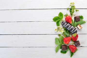 Strawberries with sweets. On a white wooden background. Top view. Copy space.