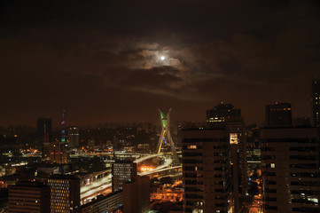 Night view of the city skyline with bridge and buildings under cloudy and full moon in the city of São Paulo. The gigantic city, famous for its cultural and business vocation.