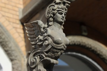 Sirenen-Skulptur an einer Hauswand