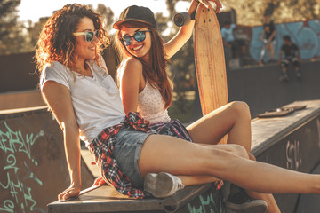 Two female skaters best friends hangout at the skate park on sunset .Laughing and fun.