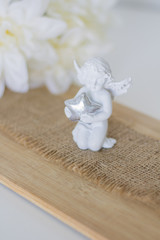 Beautiful composition, A figurine is an angel on wooden backgroun