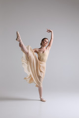 Making a dance! Graceful attractive charming young ballerina in beige outfit posing on toes on the studio background.