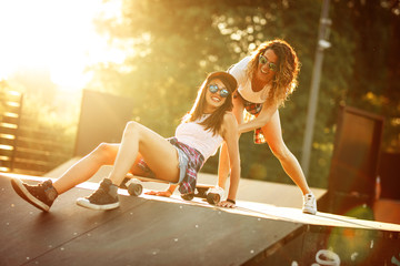Two female friends playing with skateboard at the skate park.One girl pushing other from behind.Laughing and fun.