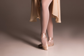 Step up! Close up picture of the feet of young ballerina wearing the beige ballet shoes and standing in pointe position.