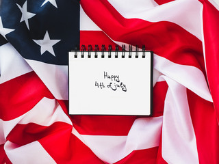 Notepad with an inscription on July 4th against the background of the US flag. Preparation for the Independence Day. Top view, close-up. The concept of an independent, strong country and nation