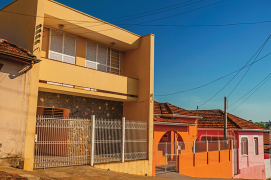 Working-class colored houses and fences in an empty street at São Manuel. A cute little town in the countryside of São Paulo State. Southeast Brazil. Retouched photo.