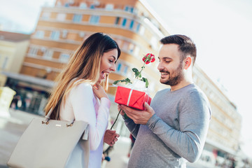 Man surprises woman with a gift and rose in the city