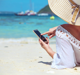 Relaxed lady using a smartphone on a tropical beach