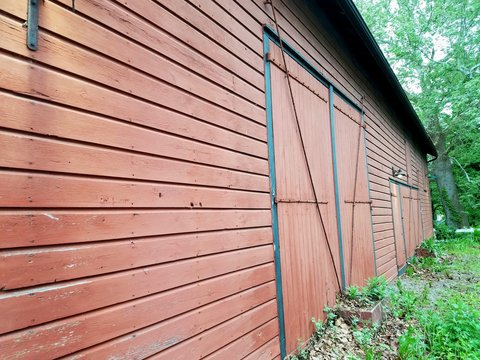 Long Side Perspective of a Rustic Red Barn Door and the Outside Walls