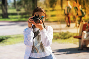 A girl in white clothes and blue glasses with a professional camera takes pictures on a bright sunny summer afternoon in the park