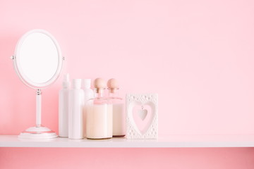 Soft pink light bathroom decor for advertising, design, cover. Cosmetic set on light dressing table,  mirror on a wooden shelf. mock up