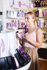 adult girl choosing toys in sex shop.