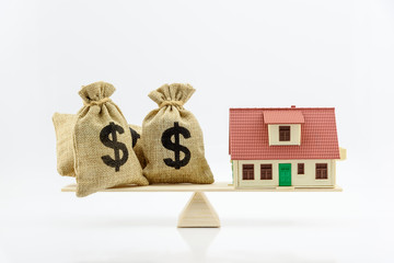 Home loan / reverse mortgage or transforming assets into cash concept : House model, US dollar notes in hessian bags on a simple balance scale, depicts homeowner or borrower turns properties into cash
