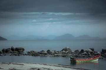 Dark moody tranquil landscape tropical beach sunset island sea boat