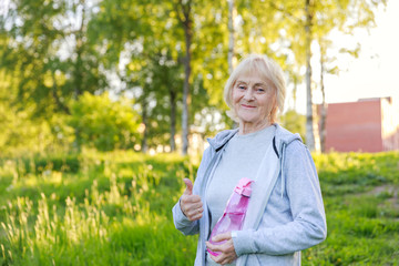 Happy elderly woman shows thumbs up in sportswear in a sunny park. Be active and energetic until old age, longevity, biohacking