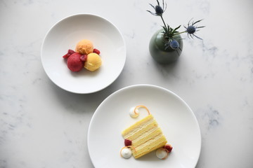 Sorbet with raspberries and yellow sponge cake slice on plates