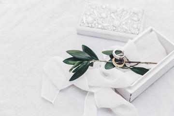 Wedding rings on bright background, boho style