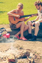 Young couple camping playing guitar outdoor