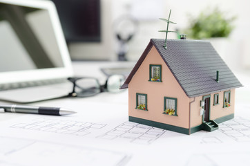 House model on desk, mortgage or house building concept