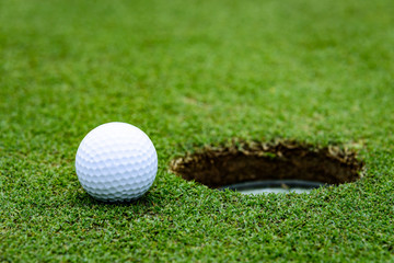 Close up side view of a golf ball on a putting green next to the hole