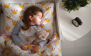child  girl sleeps in her bed with toy teddy bear  in morning.