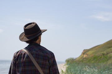 fada0a984ab Back view of young male hiker in cowboy hat walking outdoors in summer day.  Hipster