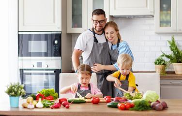 happy family with children preparing vegetable salad .