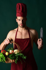 Bearded male chef holds knife. Professional food preparation concept. Man in cook hat and apron with knife. Food. Cooking. Preparation and culinary concept. Bearded chef holds basket with vegetables.