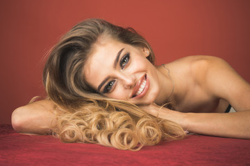 Sensual elegant glamour woman fashion model. Haircare, skincare, cosmetic&beauty concept - sexy smiling model with gorgeous healthy shiny blond long hair, perfect makeup, bare shoulders lies on table.