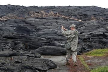 Tech Sgt. Andrew Lee Jackson, of the Hawaii National Guard, takes photos of the Kilauea lava flow, in Leilani Estates near Pahoa, Hawaii