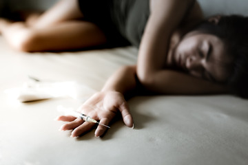 The junkie woman or drug addict girl is putting hand on bed and puts injection needle contain heroin or narcotic on her hand. Poor girl lay down on bed and get drunk or unconscious at dark room.