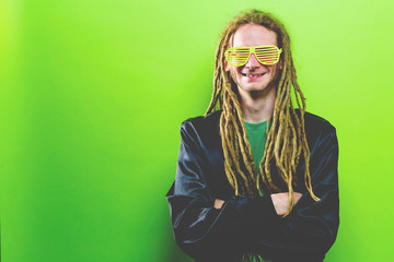 Funky fashion man with dreadlocks on a solid colored background