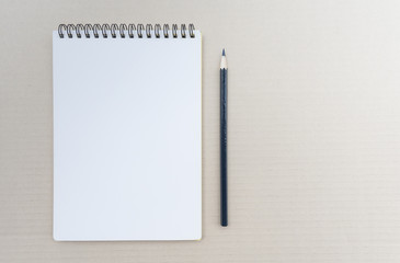 Top view of open spiral blank notebook with pencil on brown background.