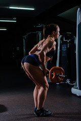 A strong, muscular, girl in black shorts, performs an exercise of deadlift, with a sports bar. Dark gym.